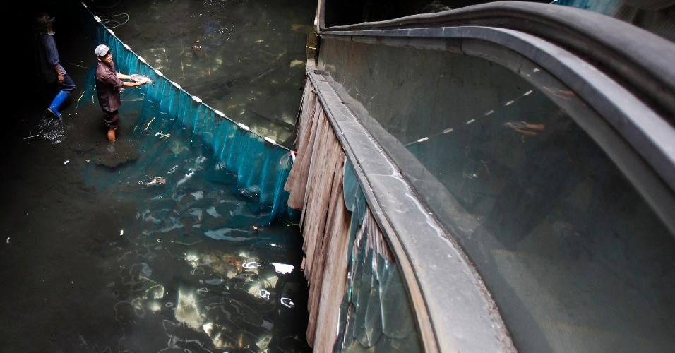 """13.jan.2015 - Funcionários da Administração Metropolitana de Bancoc (BMA, na sigla em inglês) """"pescam"""" no shopping abandonado New World Mall, em Bancoc, Tailândia"""