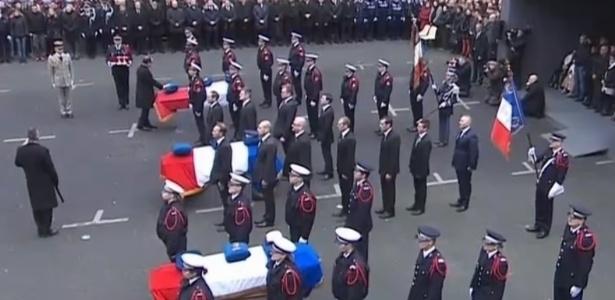 13.jan.2015 - O presidente da França, François Hollande (à esq. tocando um dos caixões), participa na manhã desta terça-feira (13) de homenagem aos três policiais mortos durante os atentados terroristas ocorridos na semana passada em Paris: Franck Brinsolaro, Ahmed Merabet e Clarissa Jean-Philippe