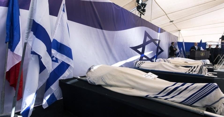 13.jan.2015 - O primeiro-ministro de Israel, Benjamin Netanyahu (direita), discursa perto dos corpos cobertos de Yohan Cohen, Yoav Hattab, Philippe Braham e François-Michel Saada, vítimas do ataque de sexta-feira (9) em uma mercearia de Paris, durante o funeral conjunto em Jerusalém