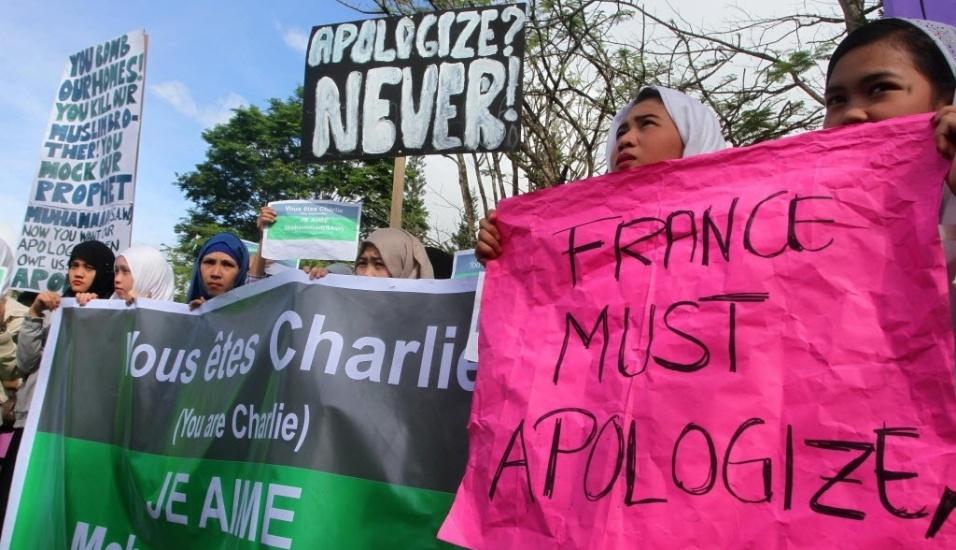 """14.jan.2015 - Cerca de 1.500 pessoas protestaram em Marawi, uma das principais cidades de maioria muçulmana das Filipinas, contra as charges do profeta Maomé publicadas na revista satírica francesa """"Charlie Hebdo"""". Na imagem, jovem segura cartaz rosa no qual exige que a França peça desculpas pelas caricaturas"""