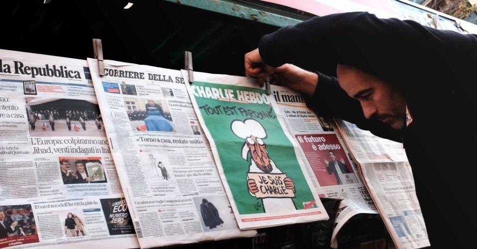 """14.jan.2015 - Dono de uma banca de jornal exibe nesta quarta-feira (14) a nova edição da revista satírica """"Charlie Hebdo"""" em Roma, na Itália. A publicação desta quarta, a primeira após o ataque jihadista que matou parte da equipe da revista na semana passada, esgotou em minutos nas bancas da França. Este número, chamado """"a edição dos sobreviventes"""", terá uma tiragem de cinco milhões de exemplares, dois milhões a mais do que o previsto anteriormente, anunciou hoje a distribuidora da publicação, a MLP"""