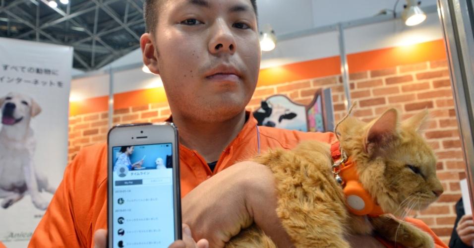 """14.jan.2015 - Gato usa o dispositivo de comunicação """"Tsunagaru-call"""", desenvolvido pela empresa japonesa Anicall, durante o Expo Device Technology Wearable, realizado em Tóquio, Japão. O aparelho grava as pegadas dos animais de estimação e seus proprietários podem procurá-los com seus smartphones. As vendas se iniciam a partir de março"""