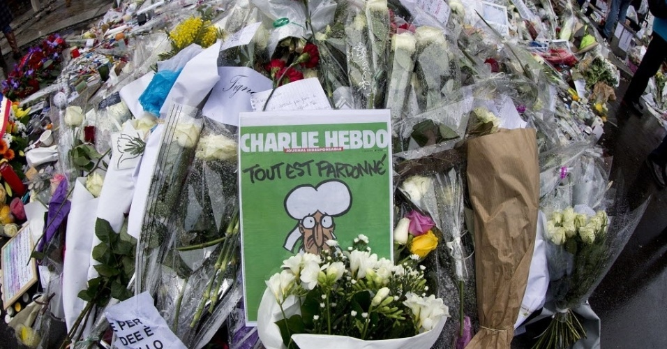 """14.jan.2015 - Um exemplar da última edição da """"Charlie Hebdo"""" é colocado entre os tributos em frente à sede da revista em Paris, na França. A revista esgotou em questão de minutos em quiosques de todo o país"""