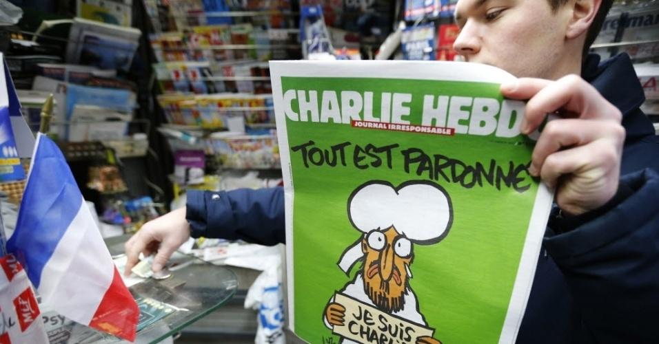 """14.jan.2015 - Um homem segura nesta quarta-feira (14) um exemplar da nova edição da revista """"Charlie Hebdo"""", a primeira depois que dois homens invadiram o escritório da publicação na semana passada e mataram 12 pessoas, em Paris, na França. Em um gesto de desafio à intolerância religiosa, a edição traz na capa uma caricatura do profeta Maomé, o que trouxe preocupações de novos atos de violência no país"""