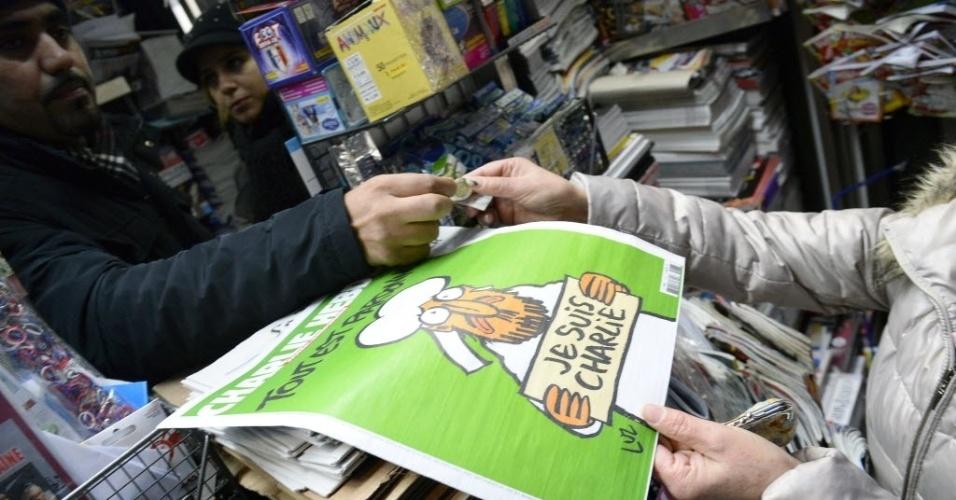 """14.jan.2015 - Uma mulher compra nesta quarta-feira (14) um exemplar da nova edição da revista """"Charlie Hebdo"""", a primeira depois que dois homens invadiram o escritório da publicação na semana passada e mataram 12 pessoas, em Paris, na França. Este número, chamado """"a edição dos sobreviventes"""", teve uma tiragem de 3 milhões de exemplares contra os 60 mil normalmente impressos, será traduzido para 16 idiomas e vendido em 25 países. Mesmo com o aumento no número exemplares, as bancas da França anunciaram que se esgotaram logo após o início das vendas, o que fez com que a distribuidora anunciasse uma nova tiragem de cinco milhões de revistas"""