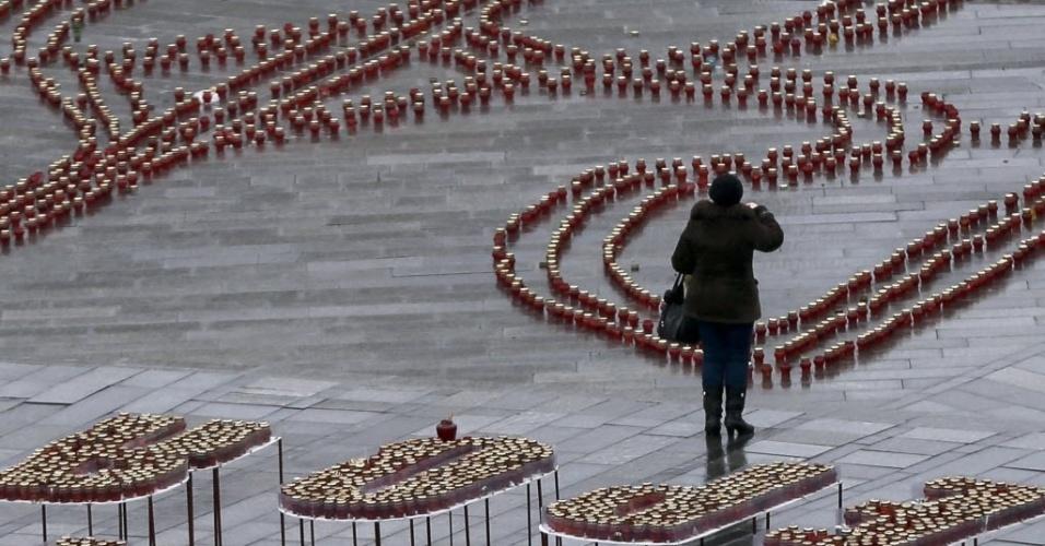 15.jan.2015 - Ucraniana reza nesta quinta-feira (15) na Praça da Independência em Kiev. O local foi enfeitado em homenagem às 11 pessoas que morreram nesta terça-feira (13) quando um ônibus de passeio foi atacado por foguetes de longo alcance na região de Donetsk