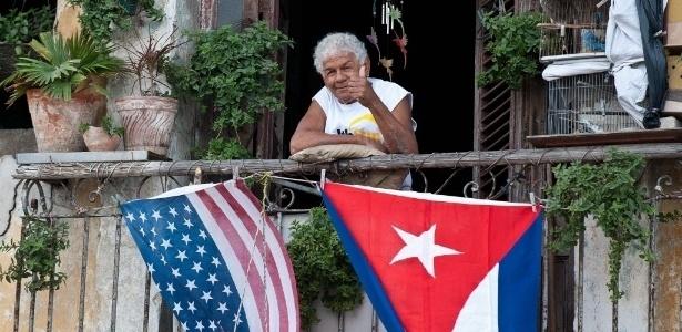 Cubano acena de sua varanda decorada com bandeiras dos EUA e de Cuba, em Havana - Yamil Lage/ AFP