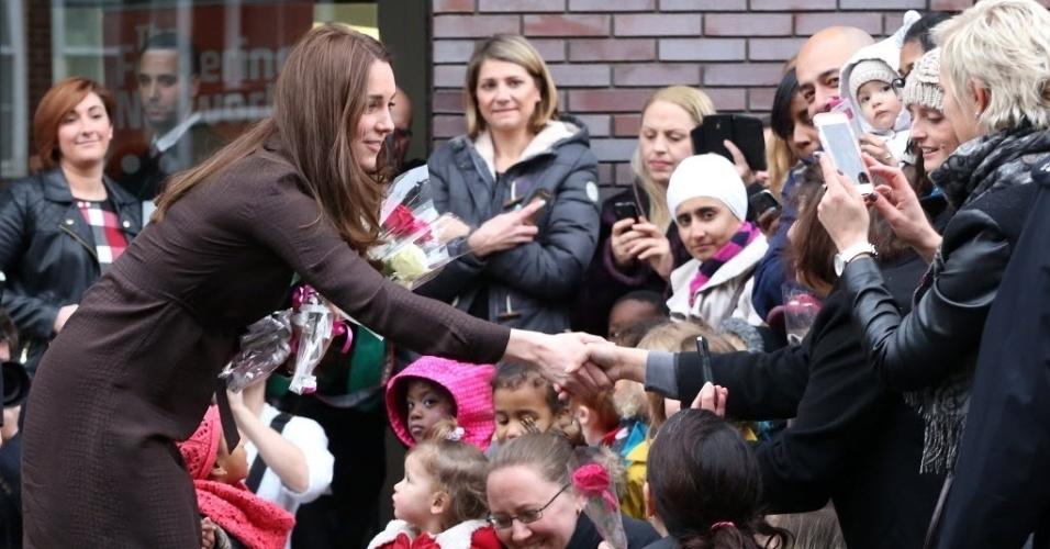 16.jan.2015 - Kate Middleton, duquesa de Cambridge, cumprimenta crianças e pais durante visita a local onde acontece o trabalho das famílias de acolhimento, que cuidam de jovens carentes, em Londres, na Inglaterra, nesta sexta-feira (16)