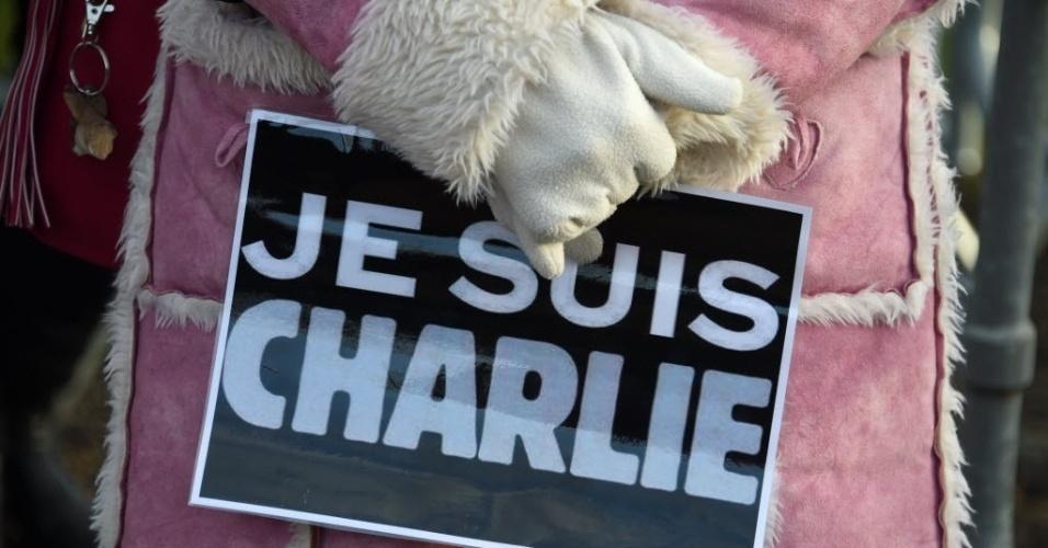 """16.jan.2015 -  Mulher carrega cartaz com a frase """"Je suis Charlie"""" (""""Eu sou Charlie""""), em homenagem às vítimas do atentado terrorista na revista """"Charlie Hebdo"""", nesta sexta-feira (16), no enterro do cartunista e editor da revista satírica, Stephane Charbonnier, em Pontoise, nos arredores de Paris, na França. O artista será enterrado em uma cerimônia íntima no cemitério da cidade. Stephane morreu no atentado que deixou 12 mortos e foi reivindicado pela Al Qaeda no Iêmen, que disse que a ação teve como objetivo vingar Maomé pelas charges ofensivas que foram publicadas"""