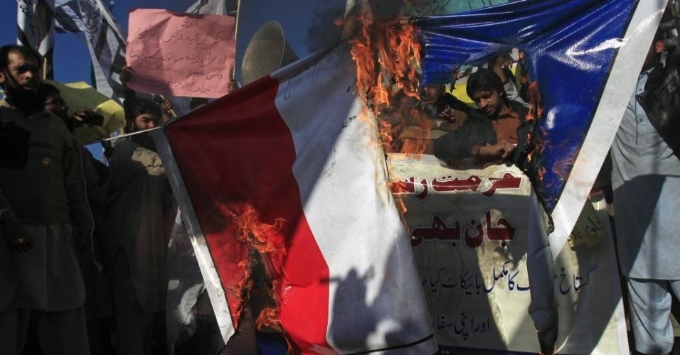 """16.jan.2015 - Paquistaneses queimam uma bandeira francesa durante um protesto contra a revista francesa """"Chalie Hebdo"""". O ato é um protesto contra a publicação de charges retratando o profeta Maomé"""