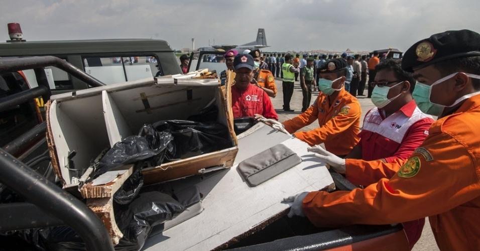 """17.jan.2015 - Diretores da agência de operações de busca e resgate da Indonésia examinam neste sábado (17) parte dos destroços do avião da AirAsia, que caiu em 28 de dezembro no mar de Java com 162 pessoas a bordo, em Surabaya, leste da ilha de Java. A fuselagem da aeronave será retirada do mar """"em breve"""", de acordo com o chefe da agência, Henry Bambang Soelistyo. Segundo ele, as equipes conseguiram visualizar outra parte da aeronave, que pode ser correspondente à cabine, um motor do Airbus320 e algumas poltronas, mesmo com as fortes correntes e a presença constante do mau tempo"""