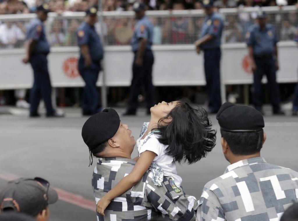 17.jan.2015 - Um soldado filipino ajuda neste sábado (7) uma jovem devota que desmaiou em Manila no meio da multidão que tenta ver o papa Francisco. Uma voluntária filipina de 27 anos morreu em Tacloban, nas Filipinas, pouco depois de o pontífice visitar a cidade, ao ser atingida por um andaime que tinha sido colocado ao lado do palco onde o papa oficiou uma missa esta manhã. Kristel Mae Padasas, morreu de traumatismo craniano por volta das 14h (local, 4h em Brasília) no Hospital de São Paulo de Tacloban, segundo a ministra da Saúde, Janette Garin