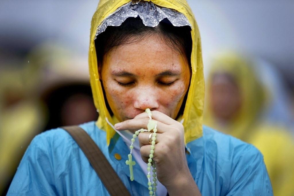 18.jan.2015 - Uma freira filipina reza neste domingo (18) embaixo da chuva enquanto acompanha a passagem do papa Francisco em Manila, nas Filipinas. Seis milhões de pessoas participaram da missa celebrada por Francisco em Manila, um recorde mundial para uma congregação papal, de acordo com a agência AFP