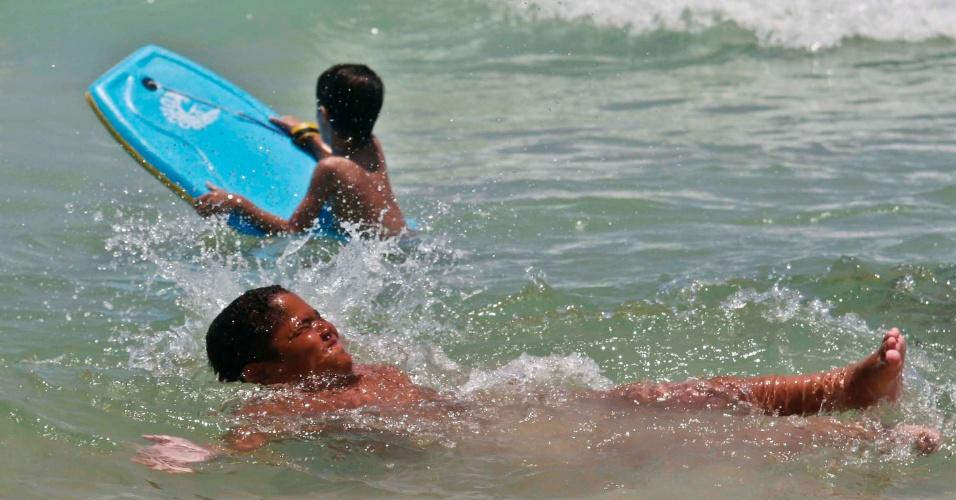 19.jan.2015 - Menino se afunda na água da praia do Pepe para suportar forte calor, na Barra da Tijuca, no Rio de Janeiro (RJ), nesta segunda-feira (19). No feriado de São Sebastião, meteorologistas preveem que a temperatura chegue aos 39ºC