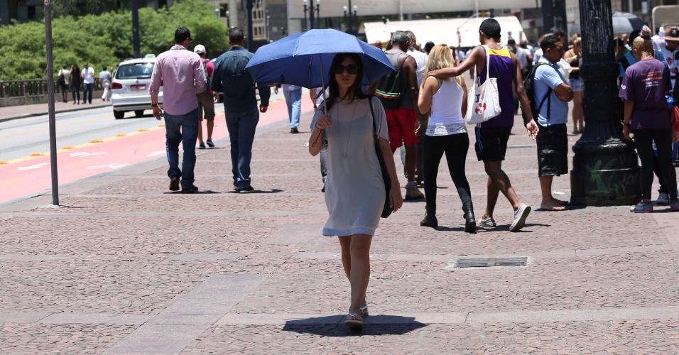 19.jan.2015 - Para enfrentar o calor, paulistana usa guarda-chuva no viaduto do Chá, no centro de São Paulo, nesta segunda-feira (19). Os paulistanos enfrentam o dia mais quente do ano hoje. A capital paulista registrou 36,5°C, a maior temperatura de 2015 e a sexta maior em 72 anos, desde que o Inmet (Instituto Nacional de Meteorologia) iniciou a contagem -- a mais alta já registrada na cidade foi 37,8°C, em 17 de outubro de 2014