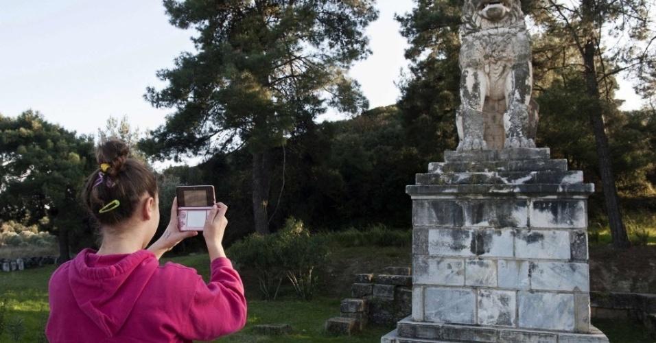 19.jan.2015 - Uma menina fotografa a estátua de um leão de mármore localizado perto do local de uma escavação arqueológica, na cidade de Amphipolis, no norte da Grécia, em 22 de novembro de 2014. A grande tumba antiga que acreditava-se poder abrigar os restos mortais de Alexandre o Grande contém ossos de uma mulher, um bebê recém-nascido e dois homens, além dos fragmentos de uma pessoa cremada, segundo o Ministério da Cultura grego
