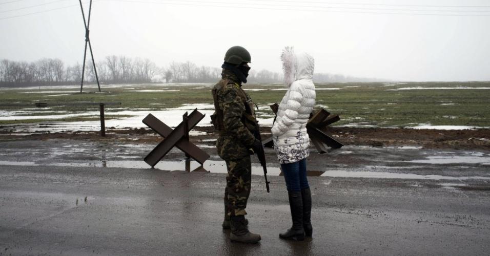 21.jan.2015 - Soldado das forças ucranianas conversa com uma mulher em posto de controle na cidade oriental de Kurakhove, perto de Donetsk, nesta quarta-feira. O presidente ucraniano, Petro Poroshenko, encurtou nesta quarta-feira sua visita ao Fórum Econômico Mundial, na estância suíça de Davos, depois que seu governo acusou forças regulares russas de atacarem suas tropas no leste da Ucrânia na terça-feira