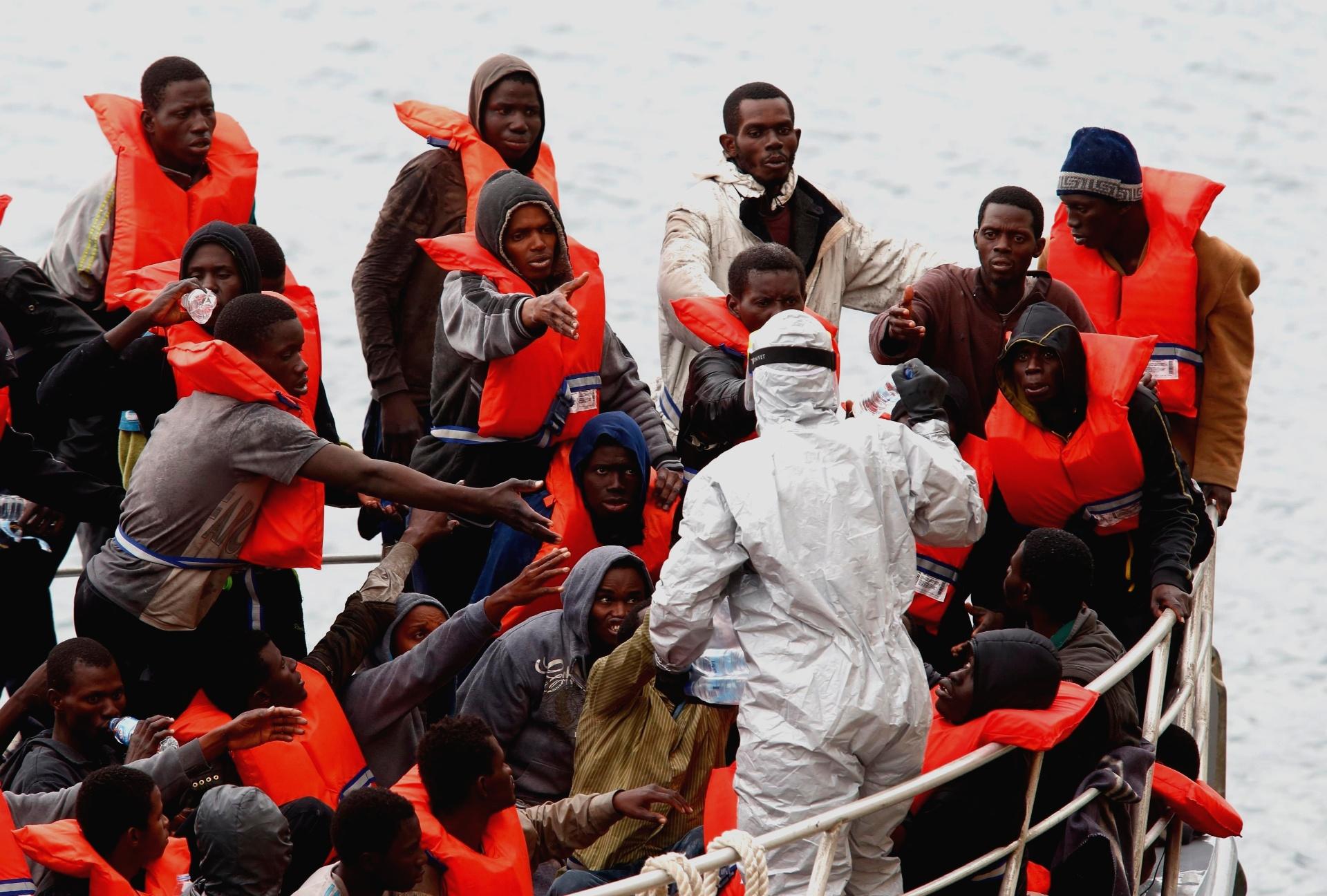 22.jan.2015 - Imigrantes resgatados em um navio-patrulha das forças armadas de Malta recebem garrafas de água de soldado com roupa anticontaminação, no porto da capital Valletta. O navio resgatou 83 imigrantes que estavam em um bote próximo à ilha, mas outros 20 podem ter morrido. Todos foram colocados em quarentena por medo do vírus Ebola