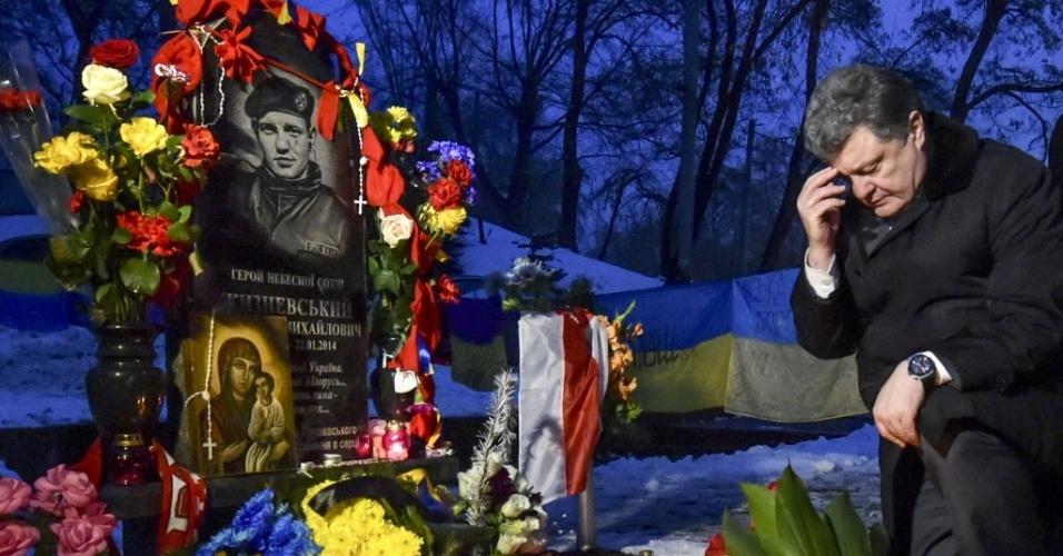 22.jan.2015 - O presidente da Ucrânia, Petro Poroshenko, se ajoelha ao lado de flores colocadas em monumento em Kiev, que homenageia manifestantes mortos durante o