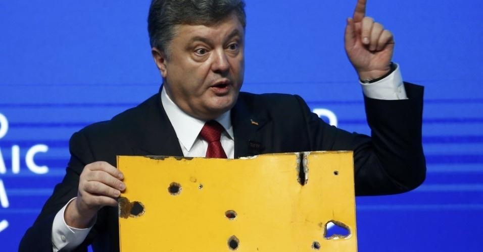O presidente da Ucrânia, Petro Poroshenko, mostra um pedaço da lataria de um ônibus civil atacado por forças russas