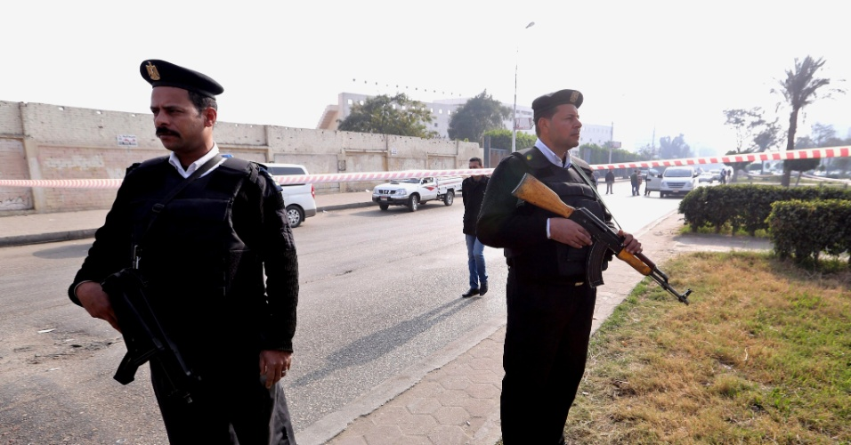 25.jan.2015 - Membros do serviço de segurança egípcio protegem local de explosão perto do distrito de Alf Maskan, no Cairo. Uma bomba caseira teria explodido próxima ao portão do clube de futebol El Shams, com o objetivo de atingir forças de segurança que guardavam o local. Dois homens ficaram feridos
