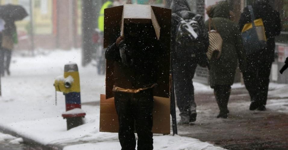 26.jan.2015 - Homem se protege da neve com caixa de papelão no bairro de Queens, em Nova York. A costa nordeste americana aguardava hoje uma colossal tempestade de neve, que já causou o cancelamento de milhares de voos e medidas de prevenção excepcionais, depois que autoridades advertiram que esta pode ser uma das nevascas