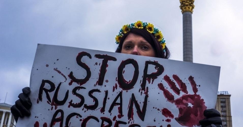 26.jan.2015 - Mulher carrega cartaz em protesto contra ofensiva no leste da Ucrânia, nesta segunda-feira (26), durante uma vigília na praça da Independência, na capital Kiev, em memória aos que perderam a vida nos ataques. Nove pessoas morreram nas últimas 24 horas nos combates, entre elas sete soldados ucranianos