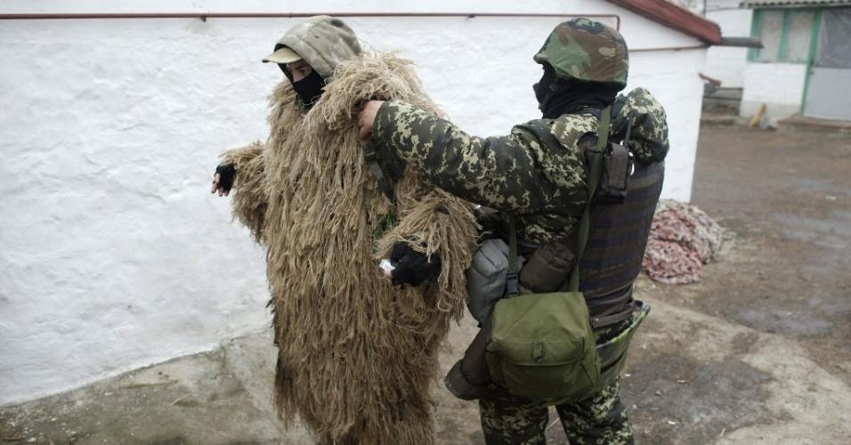 26.jan.2015 - Um soldado ucraniano ajuda outro oficial a se camuflar em um vilarejo perto de Mariupol, na Ucrânia. Pelo menos 5.100 pessoas foram mortas no leste da Ucrânia desde que os combates começaram em abril. Mariupol, uma cidade portuária estratégica localizada no Mar Negro e ainda controlada por forças da Ucrânia, foi alvo dos últimos confrontos com rebeldes