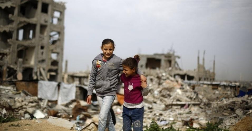 27.jan.2015 - Crianças palestinas passam, nesta terça-feira (27), por prédios destruídos ano passado durante confronto entre Israel e o Hamas na faixa de Gaza