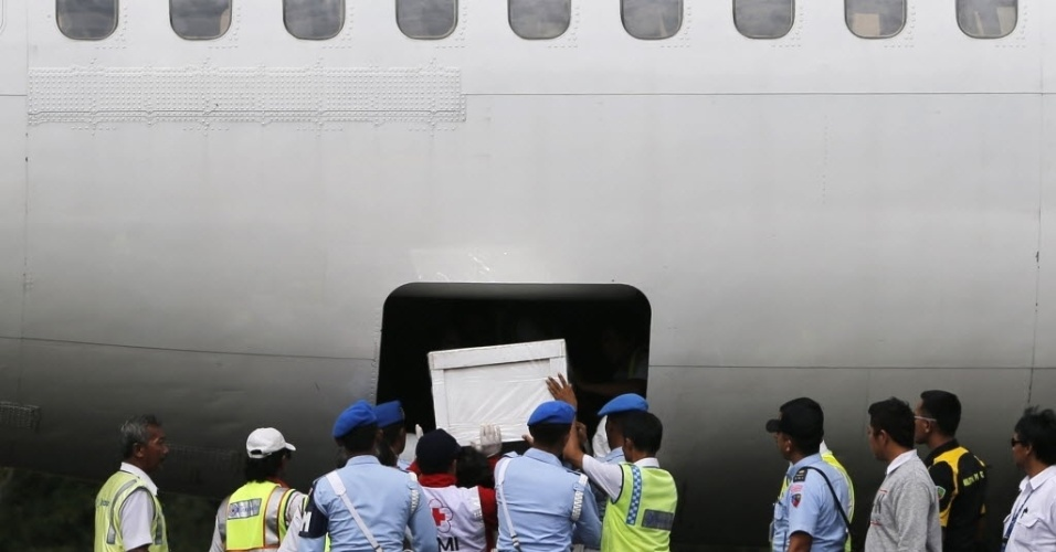 27.jan.2015 - Soldados e equipes de resgate da Indonésia colocam caixão de um passageiro do voo QZ8501 da AirAsia no compartimento de carga de um avião na base aérea de Iskandar, em Pangkalan Bun, na Indonésia, nesta terça-feira (27). O avião da companhia caiu em dezembro e matou 162 passageiros