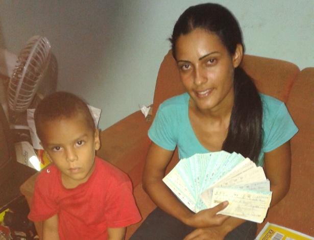 Ana Maurícia, ao lado do filho, mostra cheques encontrados no lixo; ela deve ganhar agora um novo emprego - Jornal de Barretos