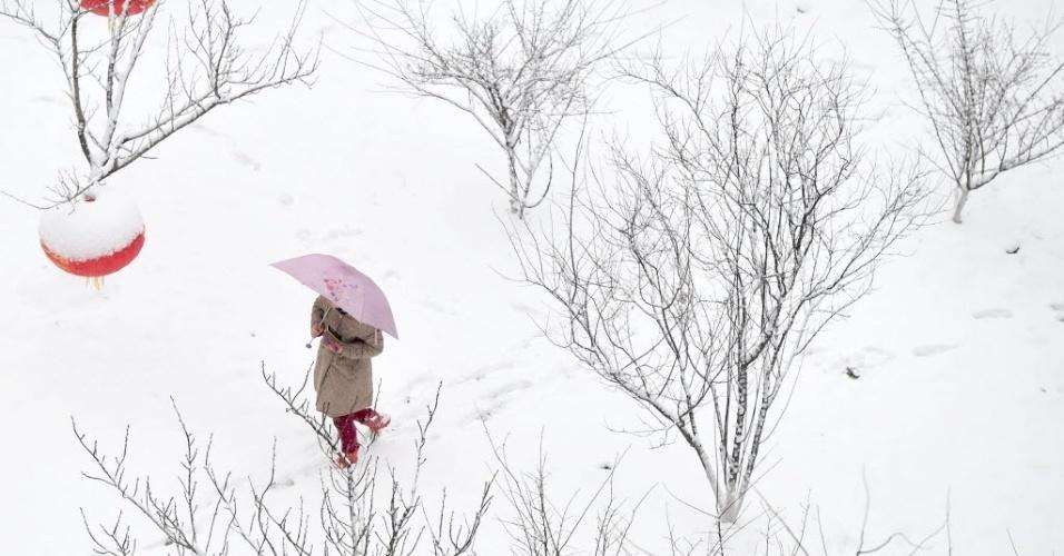 28.jan.2015 - Moradora usa um guarda-chuva para se proteger enquanto caminha por estrada coberta de neve em Hefei, capital da província de Anhui, no leste da China. Meteorologistas emitiram um alerta para tempestade de neve em algumas partes de Anhui, incluindo Hefei