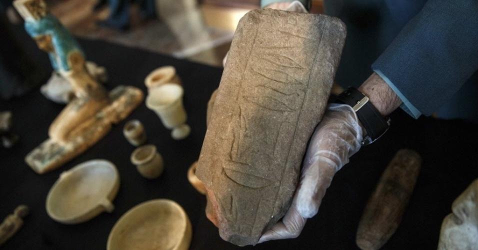 28.jan.2015 - Segurança exibe uma das 36 peças arqueológicas egípcias expostas pelo Museu Arqueológico Nacional de Madri, nesta quarta-feira (28). Os objetos foram saqueados dos sítios arqueológicos de Saqqara e Mit Rahina, e foram recuperados no porto de Valência, na Espanha