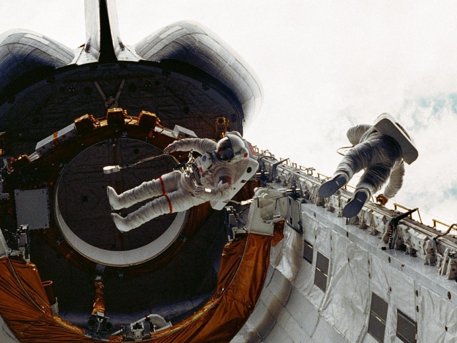 Os astronautas Story Musgrave (esq.) e Don Peterson trabalham na área de carga do Challenger durante caminhada espacial em 7 de abril de 1983