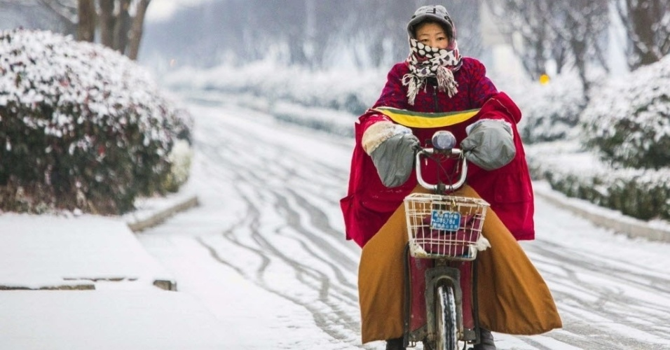 28.jan.2015 - Moradora se protege do frio com casacos e sacos plásticos enquanto anda de bicicleta em uma rua coberta pela neve em Lianyungang, província de Jiangsu, na China