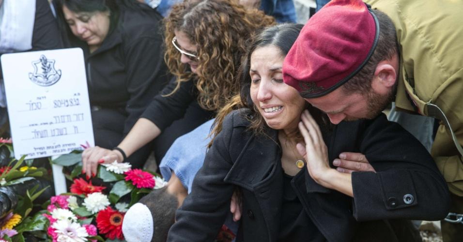 29.jan.2015 - Parentes do sargento israelense Dor Chaim, 20, um dos soldados mortos em ataque de míssil do Hezbollah a um comboio na fronteira do Líbano, colocam flores sobre o caixão no cemitério de Shtulim, na cidade costeira de Ashdod, nesta quinta-feira (29)