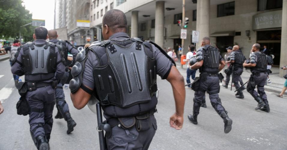 30.jan.2015 - Policiais correm durante protesto contra aumento das tarifas do transporte público na Candelária, centro do Rio de Janeiro, nesta sexta-feira (30). Houve confronto entre manifestantes e policiais, quando manifestantes tentaram furar o bloqueio feito pela polícia para evitar que pulassem as catracas