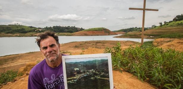 Carlos de Almeida, 50, morador de Igaratá (SP), exibe uma foto da antiga cidade, inundada desde março de 1969 - Tiago Queiroz/Estadão Conteúdo