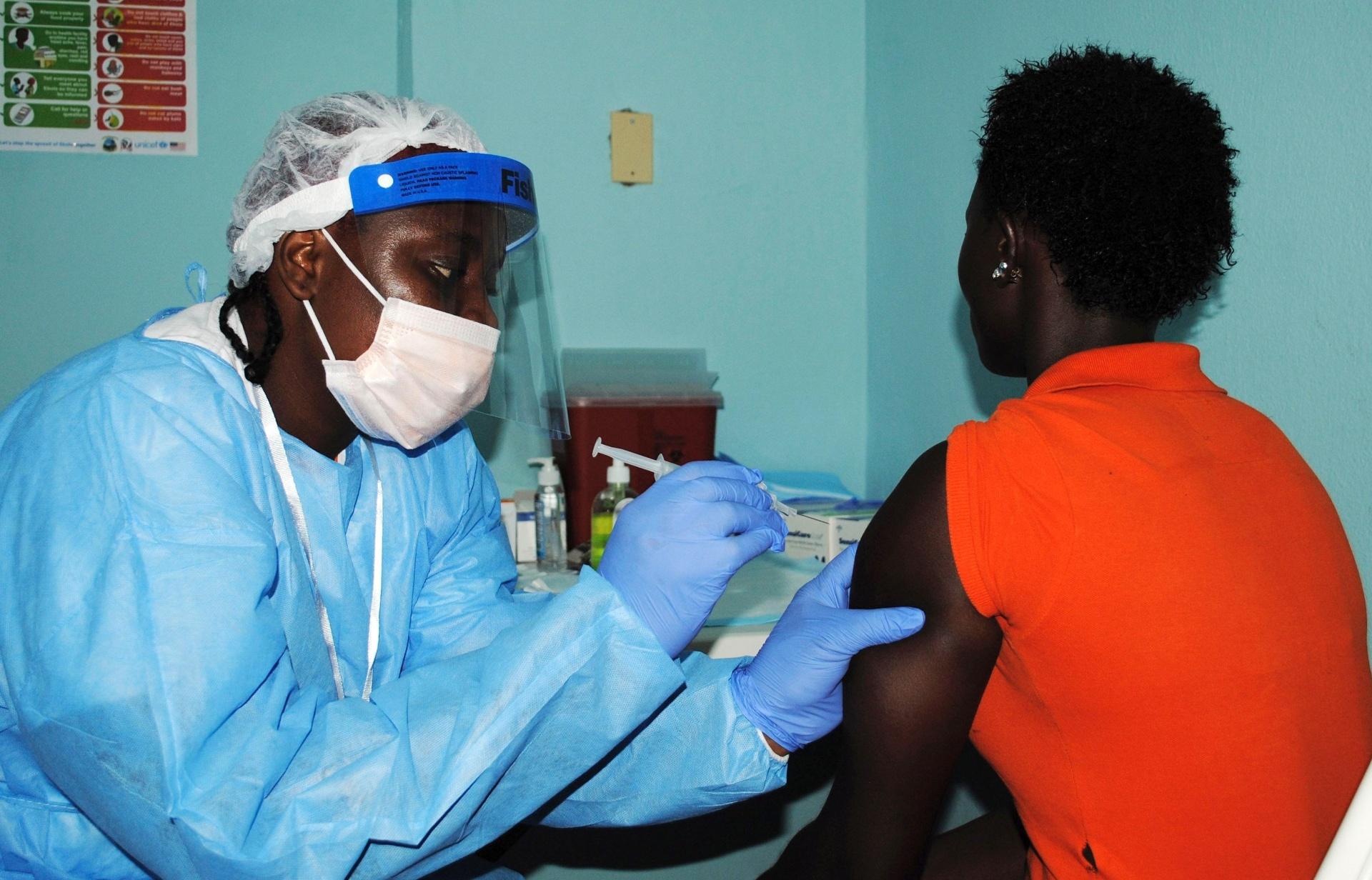 2.fev.2015 - Agente de saúde aplica vacina teste contra ebola em uma mulher durante teste em Monrovia. A Libéria vai testar a vacina contra ebola em 10 mil voluntários, como parte de um esforço para diminuir a propagação do vírus