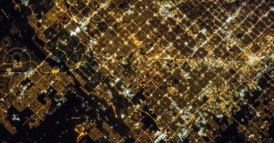 2.fev.2015 - Membros da tripulação da expedição 35 da Estação Espacial Internacional usaram uma câmera fotográfica com uma lente de 400 milímetros para fazer esta imagem noturna da área de Phoenix, no Estado americano do Arizona em 16 de março de 2013. A imagem detalhada mostra blocos da cidade e ruas durante à noite. Por conta do crescimento do uso do automóvel pessoal durante o século 20, a área metropolitana de Phoenix inclui 25 outros municípios ligados por ruas e rodovias. Do lado inferior esquerdo da imagem, campos agrícolas contrastam com as ruas iluminadas de empreendimentos residenciais vizinhos
