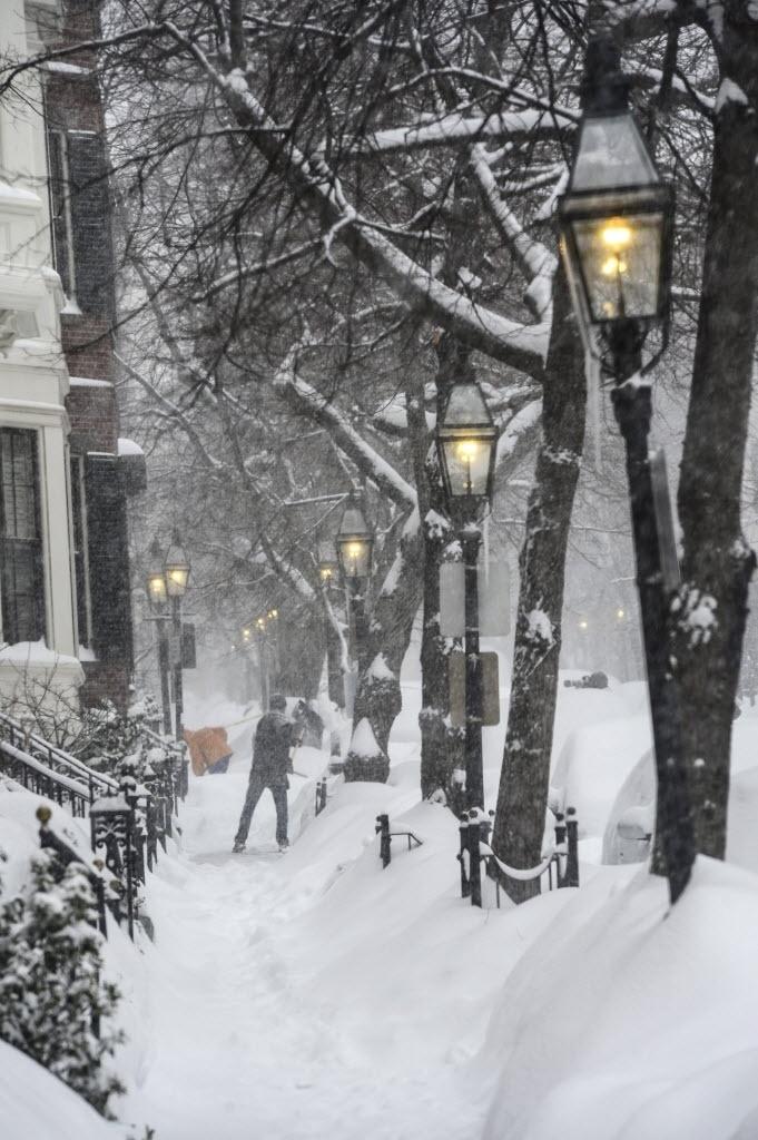 2.jan.2015 - Morador tira neve com uma pá no bairro de Beacon Hill, em Boston, nos Estados Unidos, nesta segunda-feira (2). Uma tempestade de neve atingiu a cidade na semana passada e a neve chegou a alcançar 76 centímetros. Para esta semana, a previsão dos meteorologistas é uma nova frente fria que afetará 18 Estados americanos