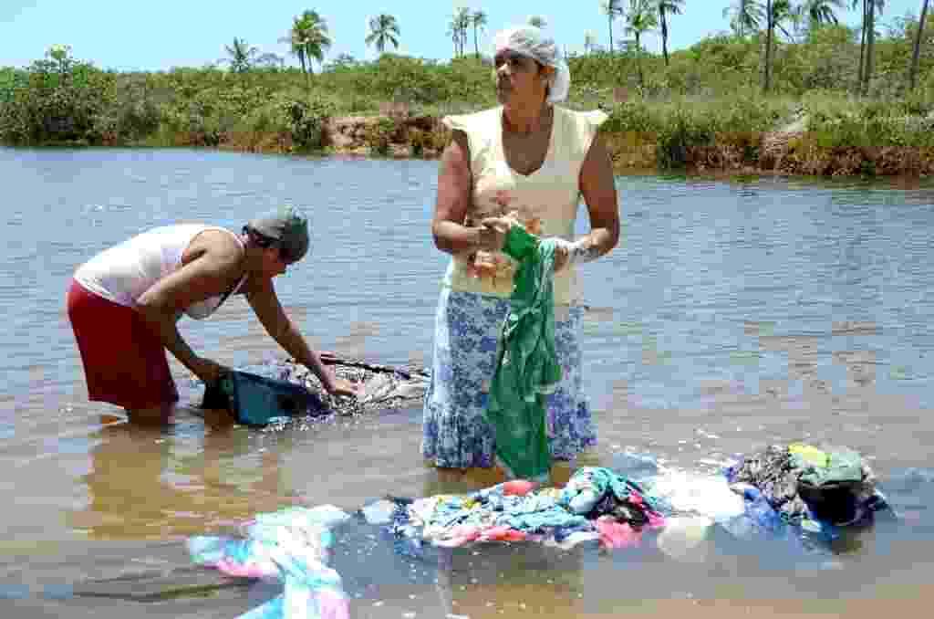 4.fev.2015 - Ângela Maria da Silva, 45, Alexandra Marques, 34, usam o rio Saúde para lavar roupa e ganhar dinheiro, em Maceió. Conhecido como paraíso das águas no Nordeste, Alagoas é o Estado que tem o menor consumo per capita do líquido no país - Beto Macário/UOL