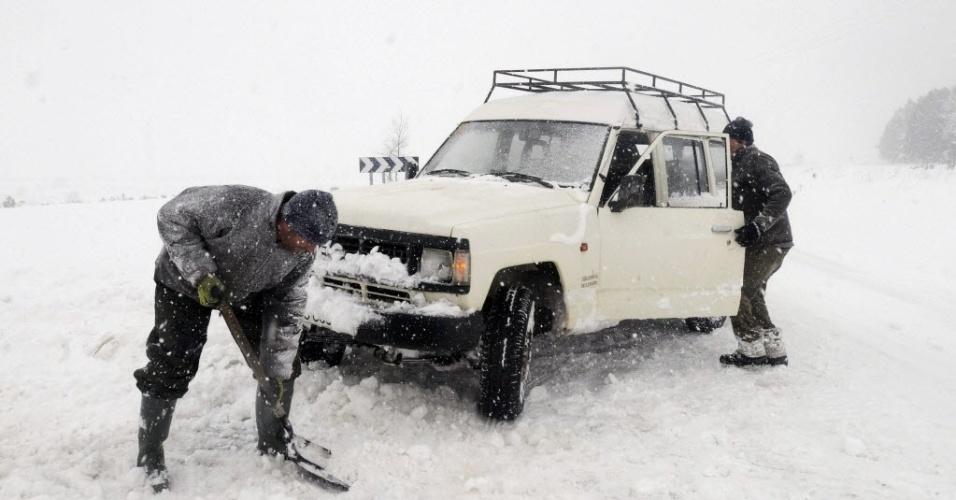 4.fev.2015 - Homens tentam retirar carro que ficou preso na neve em Leon, noroeste da Espanha. O inverno no hemisfério Norte vai até o final de fevereiro