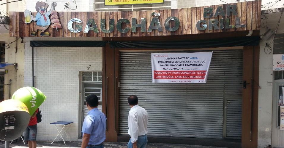 """4.fev.2015 - Pedestres passam na frente do restaurante Gauchão Grill, que amanheceu fechado nesta quarta-feira (4) devido à falta de água em São Paulo. O restaurante diminui o período de funcionamento -- antes o local abria das 11h até o último cliente e agora funcionará a partir das 15h.  """"O horário do almoço era bom, mas é na happy hour que o movimento costuma ser maior e foi essa opção que eu fiz para o prejuízo ser menor. Infelizmente."""", conta a comerciante Lidiane Vargas"""