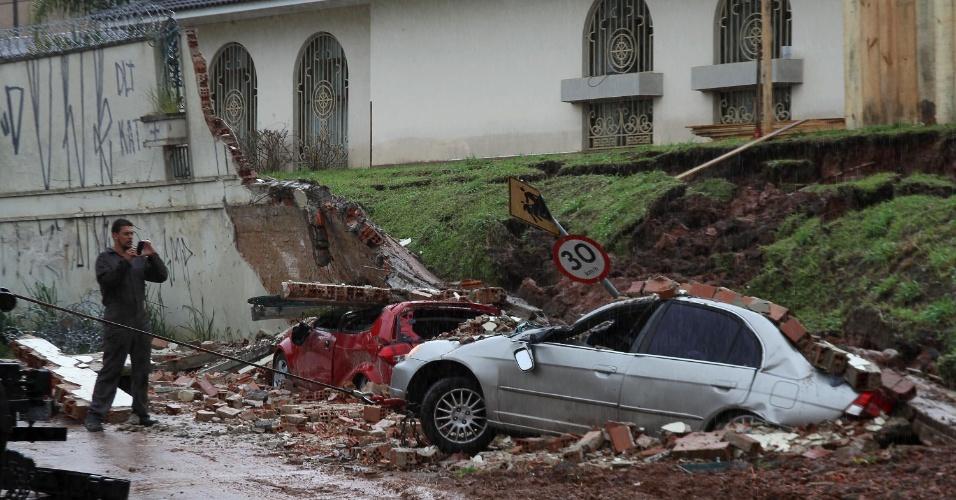5.fev.2015 - Carros foram atingidos por um muro que caiu devido ao grande volume de água durante as chuvas nesta quinta-feira (5) em Curitiba, Paraná. A rua Livio Petterle ficou bloqueada por algumas horas até a remoção dos veículos