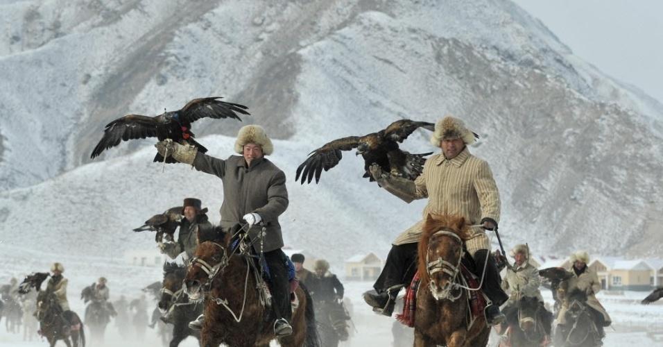 5.fev.2015 - Criadores da etnia Kyrgyz cavalgam acompanhado de seus falcões durante uma competição de caça em Akqi, na região autônoma de Xinjiang Uighur, na China. A foto foi tirada em 1° de fevereiro