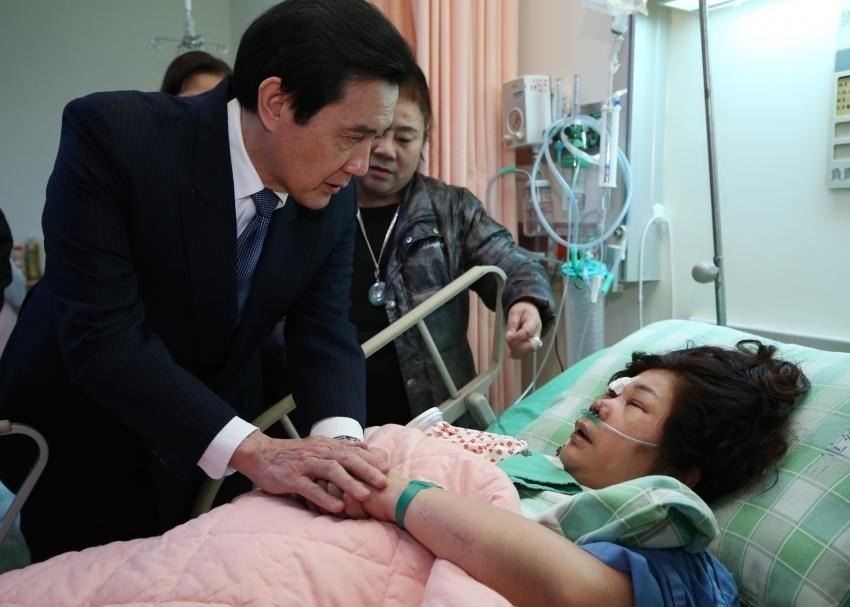 5.fev.2015 - O presidente da China, Ma Ying-jeou, conversa com uma das sobreviventes do acidente aéreo em Taipei, em Taiwan, durante visita ao hospital