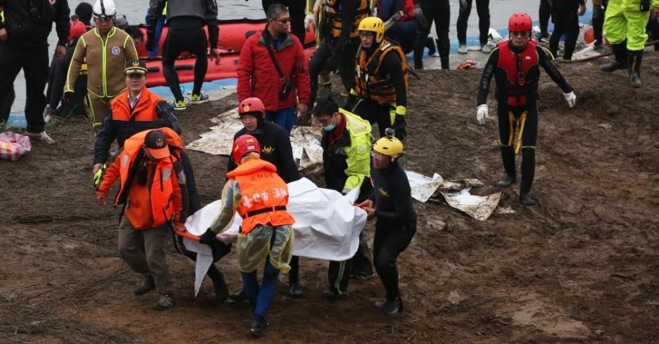 6.fev.2015 - Equipe de resgate retira corpo durante busca dos passageiros ainda desaparecidos, nesta sexta-feira (6), do acidente com o avião turboélice da TransAsia Airways no rio Keelung, em Taipé (Taiwan). O avião ATR 72-600 caiu pouco depois de decolar na última quarta-feira (4), com 58 pessoas a bordo. Ao menos 31 pessoas morreram no acidente, e 12 continuavam desaparecidas na madrugada desta sexta