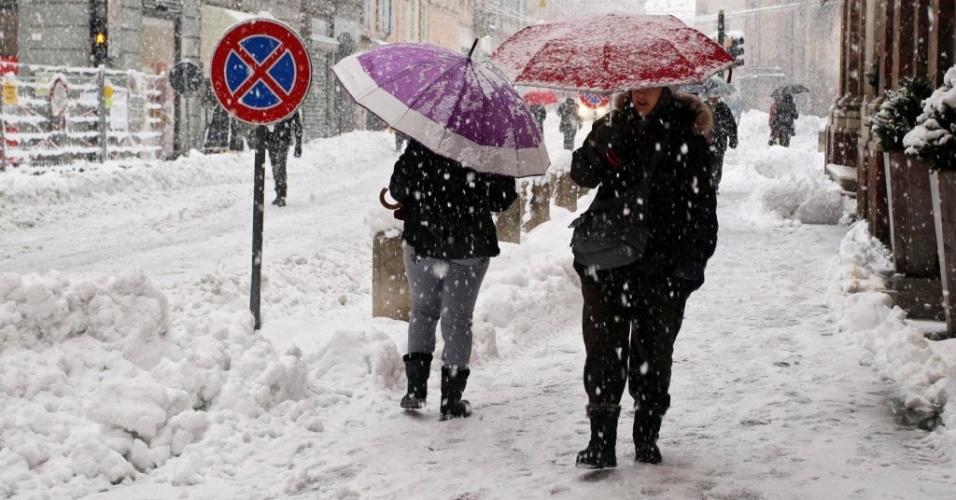6.fev.2015 - Moradores se protegem da neve com guarda-chuva em rua da cidade de Modena, no norte da Itália,  nesta sexta-feira (6). O norte do país tem sofrido com nevascas e fortes temporais