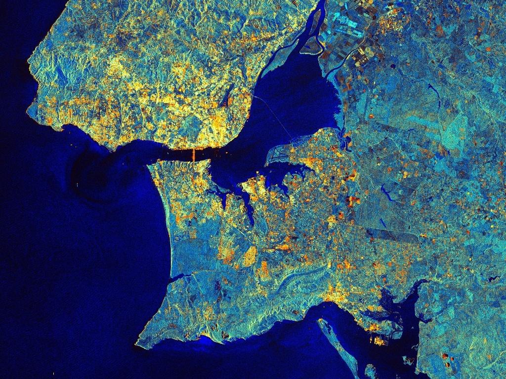 6.fev.2015 - Satélite da ESA (agência espacial europeia) exibe a região metropolitana de Lisboa, capital de Portugal. Localizado na margem norte do rio Tejo, o centro de Lisboa é repleto de edifícios e outras estruturas. Na imagem, é possível observar os reflexos da ponte pênsil que liga Lisboa a Almada